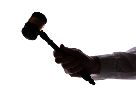 silhouette of womans hand with gavel isolated on white photo