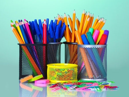 Colored holders for office supplies with them on bright background photo