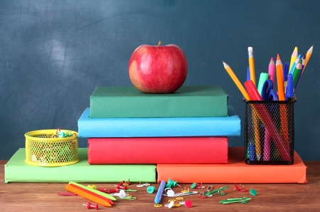 Composition of books, stationery and an apple on the teachers desk in the background of the blackboard photo