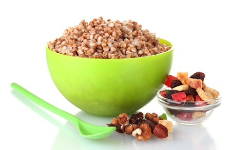 Boiled buckwheat in a green bowl isolated on white photo