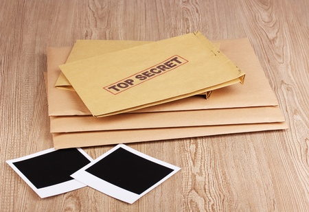 Envelopes with top secret stamp with photo papers on wooden background photo