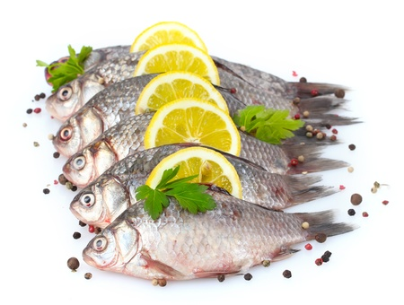 Fresh fishes with lemon, parsley and spice isolated on white Stock Photo - 13435627