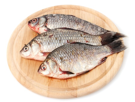 Fresh fishes on wooden cutting board isolated on white photo