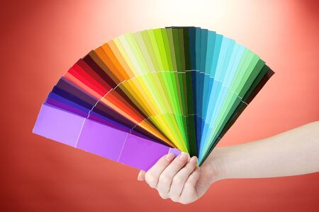hand holding bright palette of colors on red background Stock Photo - 13435763