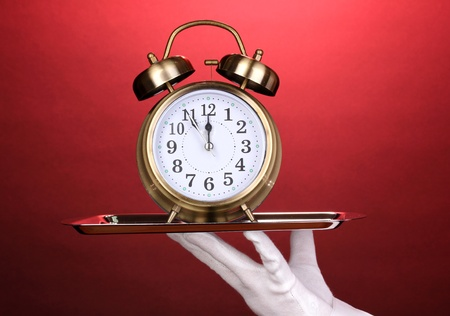 catering service: Hand in glove holding silver tray with alarm clock on red background