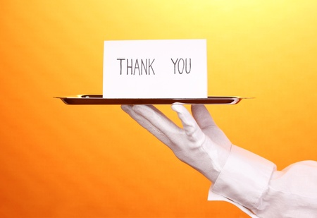 Hand in glove holding silver tray with card saying thank you on yellow background photo