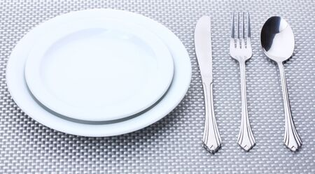 White empty plates with fork, spoon and knife on a grey tablecloth Stock Photo - 13435767