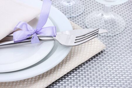 White empty plates, fork and knife tied with a ribbon and glasses on a grey tablecloth Stock Photo - 13435830
