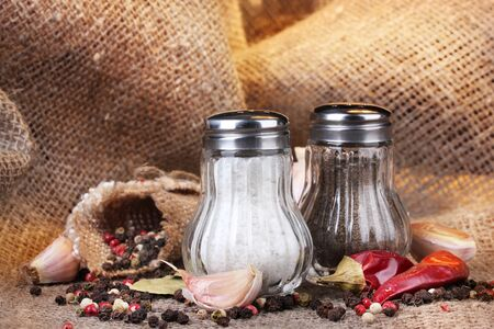 Salt and pepper mills and spices on burlap background photo