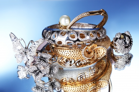 Beautiful silver and gold bracelets and rings on blue background photo