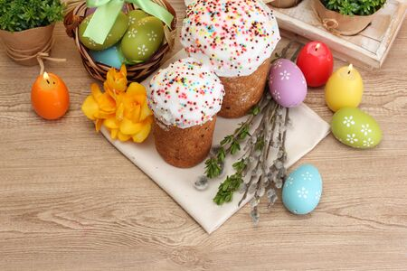 Beautiful Easter cakes, colorful eggs in basket and candles on wooden table photo