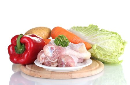 Fresh vegetables with raw chicken drumsticks on cutting board isolated on white photo