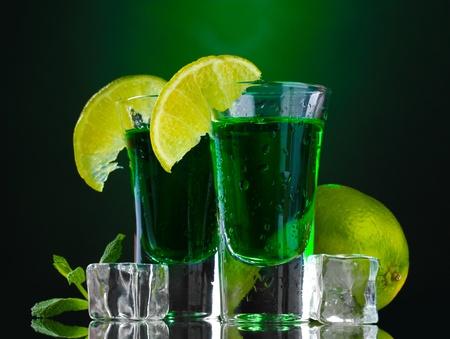 Deux verres d'absinthe, de la chaux et de la glace sur fond vert Banque d'images - 13435671