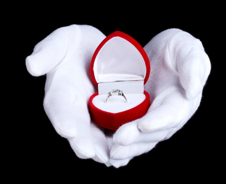 Mans hands holding ring in box on black background photo