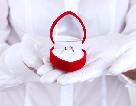 women hands holding ring in box photo