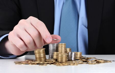 Businessman put coins isolated on white photo