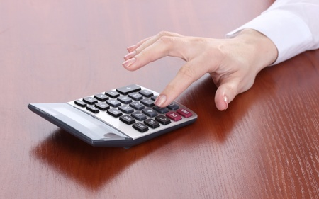 women hand and Calculator on wooden table photo