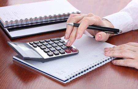 women hands with pencil, notebooks and Calculator on wooden table Stock Photo - 13435757