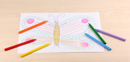 Childrens drawing of butterfly and pencils on wooden background photo