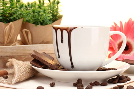 dirty cup of coffee and gerbera  beans, cinnamon sticks on wooden table photo