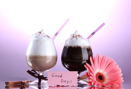 glasses of coffee cocktail and gerbera flower on violet background photo