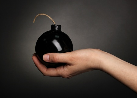 Cartoon style bomb in hand on black background Stock Photo - 13435617