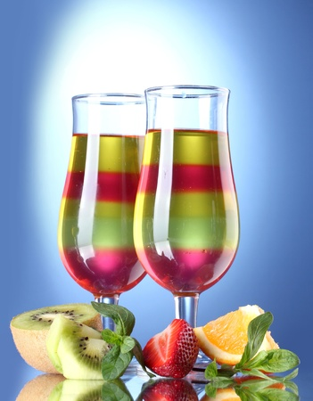 fruit jelly in glasses and fruits on blue background photo