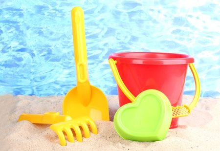 Children's beach toys on sand on water background photo