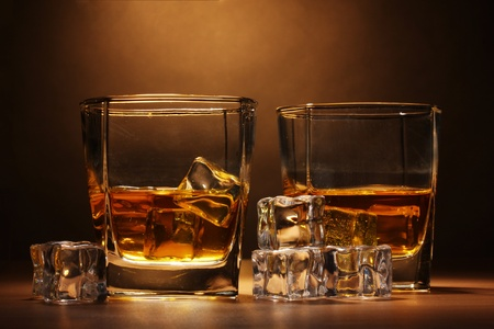 two glasses of scotch whiskey and ice on wooden table on brown background photo