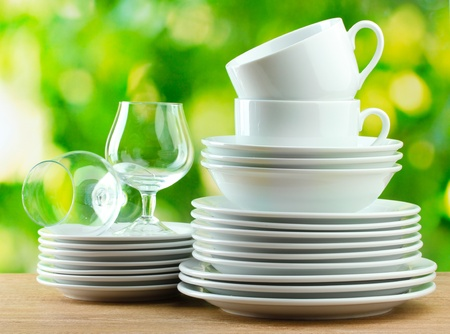 clean dishes: Clean dishes on wooden table on green background