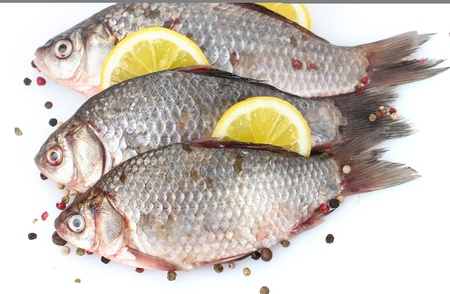 Fresh fishes with lemon and spice isolated on white photo