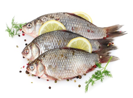 Fresh fishes with lemon, parsley and spice isolated on white Stock Photo