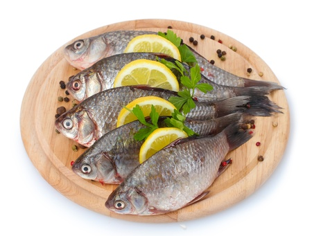 Fresh fishes with lemon, parsley and spice on wooden cutting board isolated on white photo