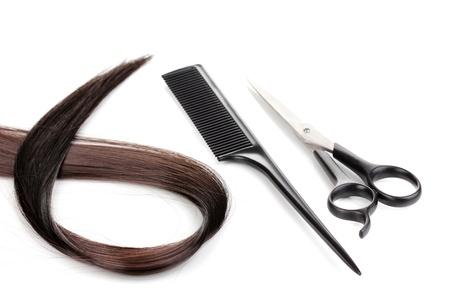 kam: Glanzend bruin haar met haar knippen schaar en kam op wit wordt geïsoleerd Stockfoto