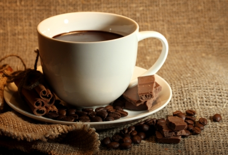 cup of coffee, beans and chocolate on sacking background photo