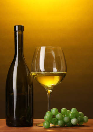 Composition of wine bottle and wineglass on wooden table on brown background photo