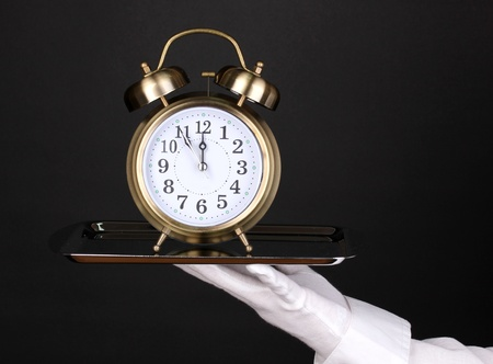 Hand in glove holding silver tray with alarm clock isolated on black photo