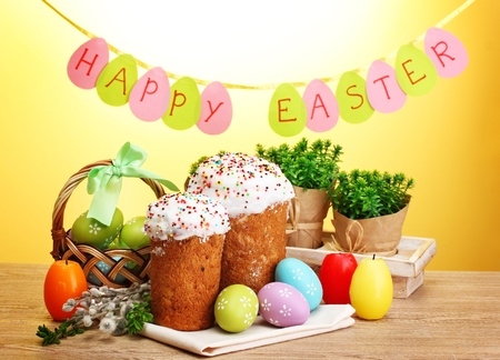 Beautiful Easter cakes, colorful eggs in basket and candles on wooden table on yellow background photo