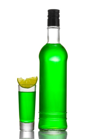 intoxicate: bottle and glass of absinthe with lime isolated on white