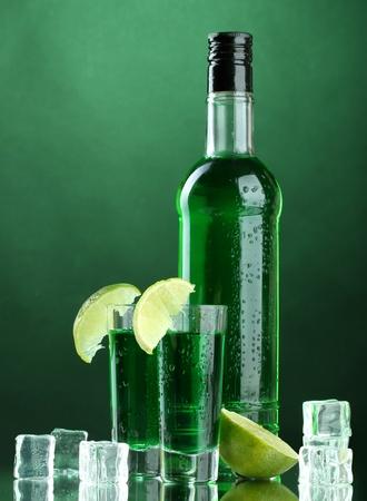 ajenjo: botella y los vasos de absenta con lim�n y hielo sobre fondo verde