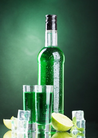 intoxicate: bottle and glasses of absinthe with lime and ice on green background Stock Photo
