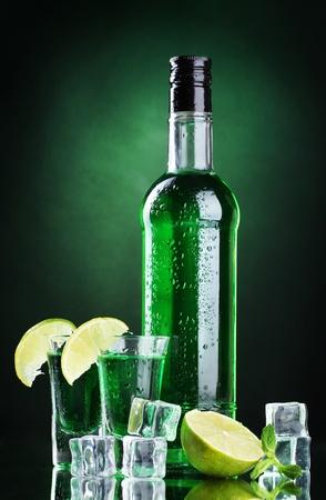 Bouteille et des verres d'absinthe avec de la chaux et de la glace sur fond vert Banque d'images - 13514956
