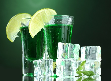 Two glasses of absinthe, lime and ice on green background Stock Photo - 13516138