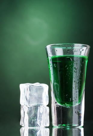 intoxicate: glass of absinthe and ice on green background