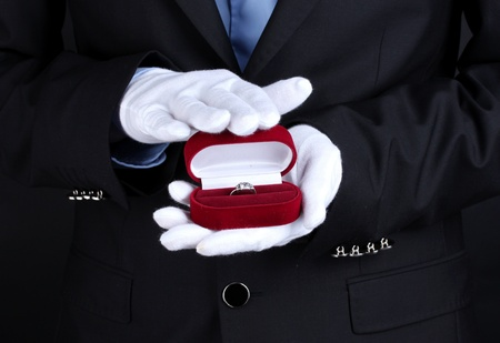 Mans hands holding ring in box photo
