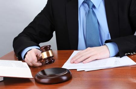 Holz-Hammer in der Hand und Bücher auf Holztisch auf grauem Hintergrund