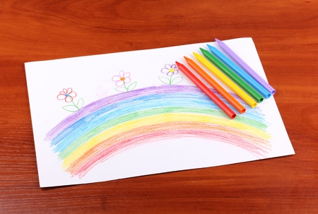Childrens drawing of rainbow and pencils on wooden background photo
