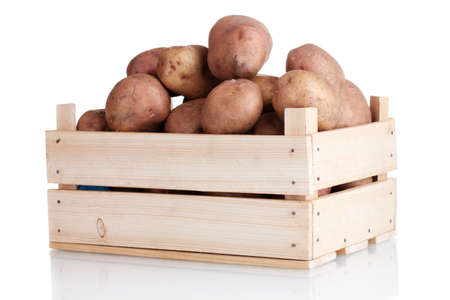 wooden box: raw potatoes in a wooden box isolated on white