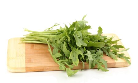 rocket lettuce: Fresh rucola salad or rocket lettuce leaves on wooden board isolated on white Stock Photo