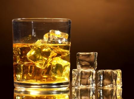 whiskey: glas whisky en ijs op bruine achtergrond Stockfoto